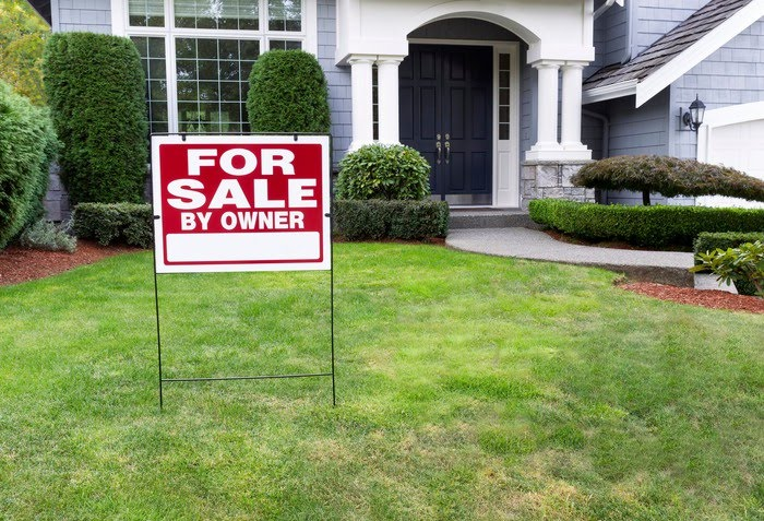 A for sale by owner sign is on the lawn in front of a house.