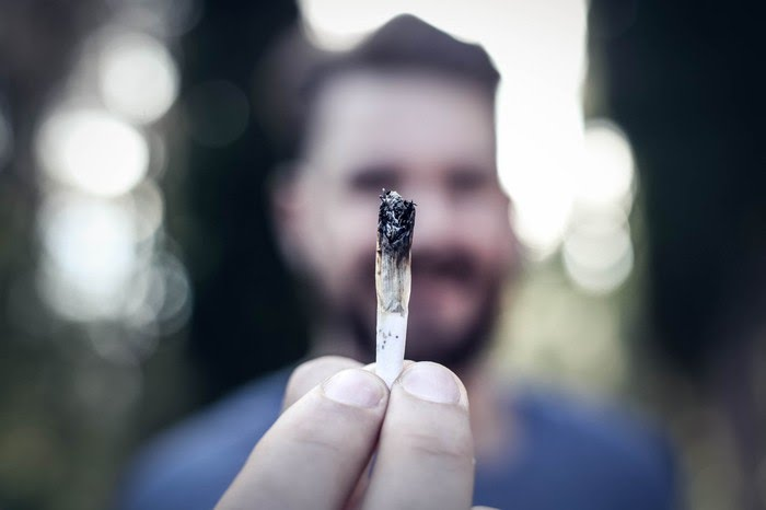 A bearded man holding a lit cannabis joint, with his arm stretched out.